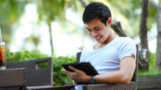Man in light blue shirt sitting outside looking at an iPad