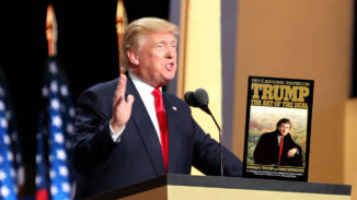 Picture of Donald Trump at a podium with one hand up and the other hand on The Art of the Deal.